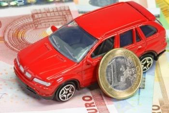 Rotes Spielzeugauto mit Banknoten